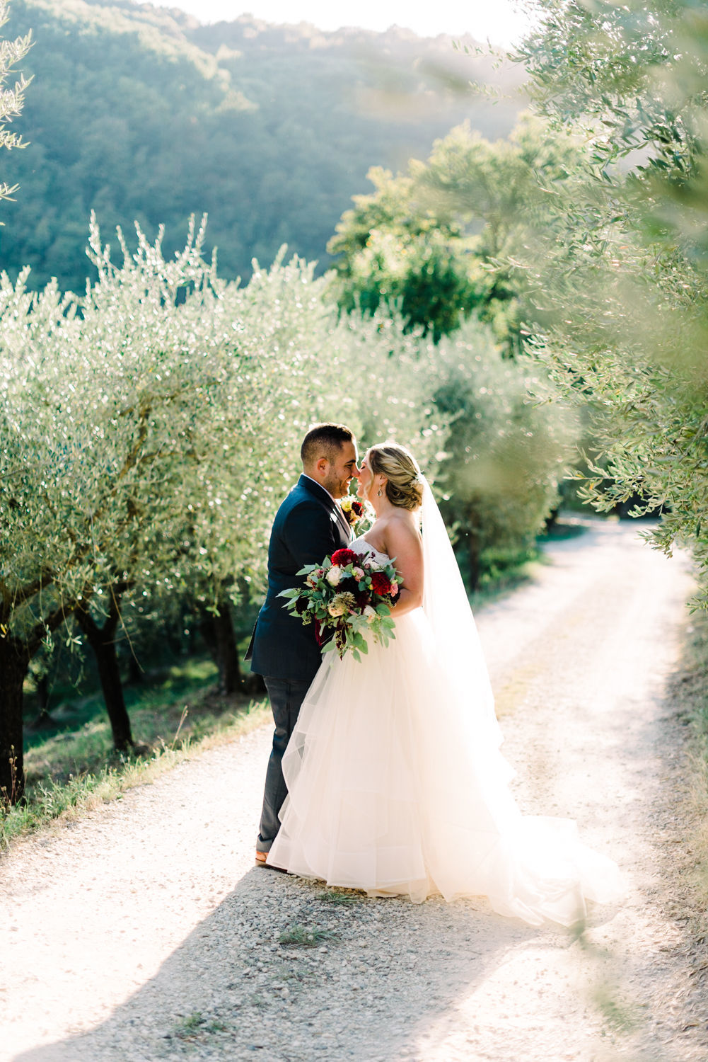 Tuscan countryside wedding with bride and groom portraits in olive tree grove