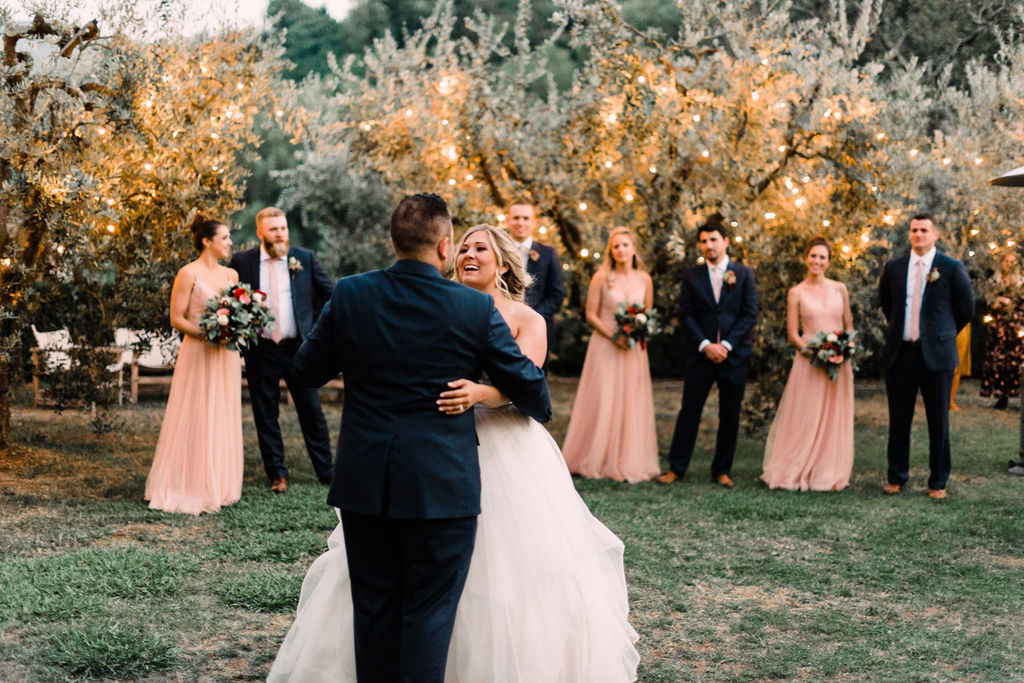strapless ruffled wedding dress with tulle skirt and custom navy groom suit first dance