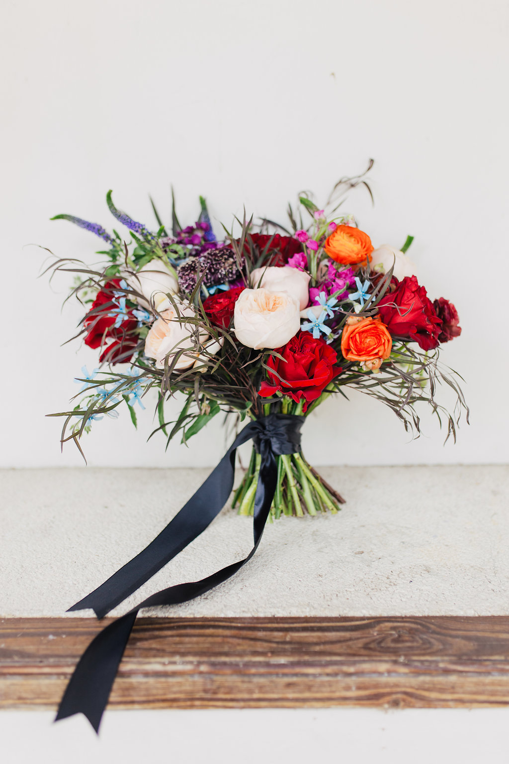 colorful bouquets with red and orange - photo by Alondra Vega Photography https://ruffledblog.com/jewel-toned-wedding-ideas-with-a-surprise-proposal