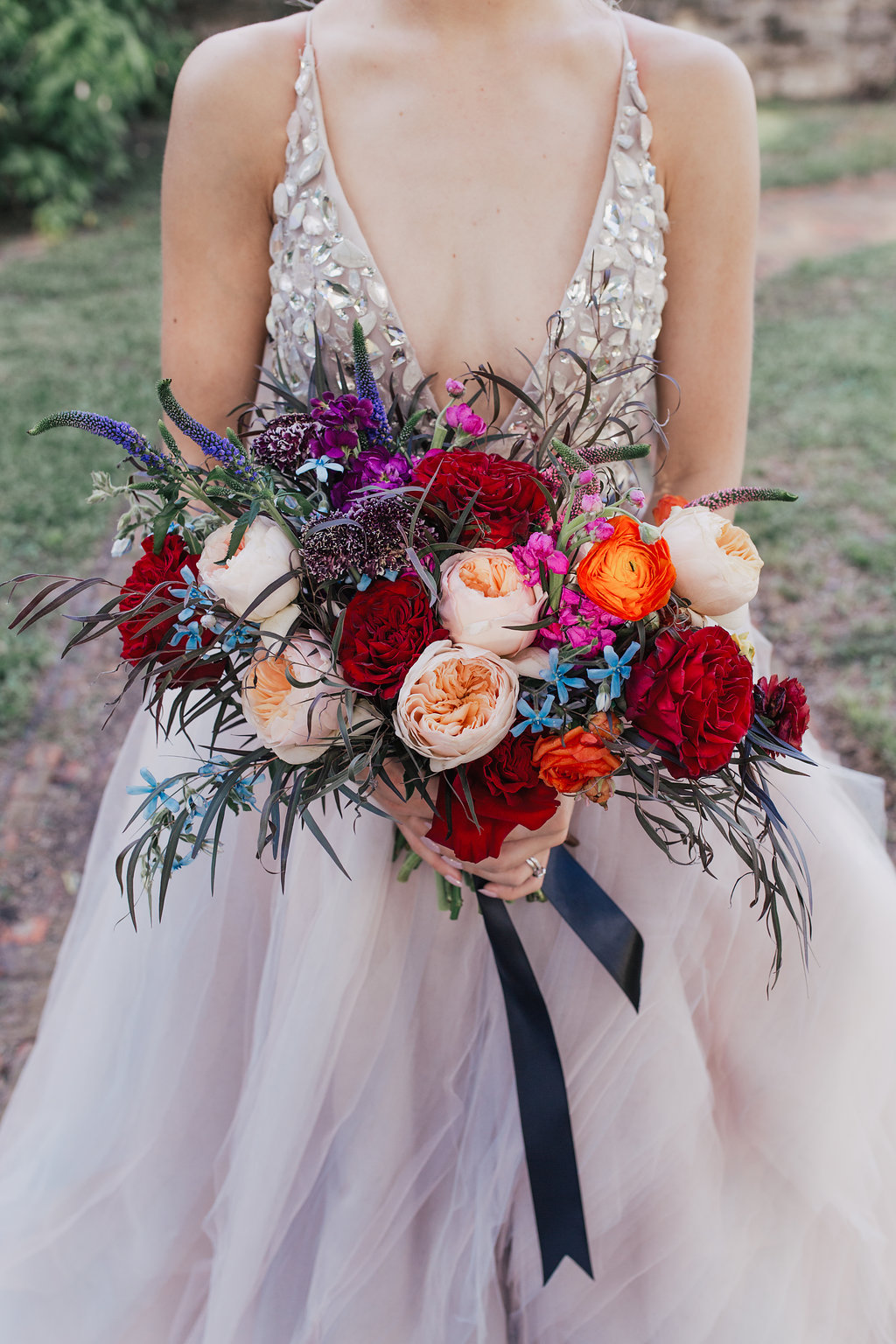 red and orange bouquets - photo by Alondra Vega Photography https://ruffledblog.com/jewel-toned-wedding-ideas-with-a-surprise-proposal