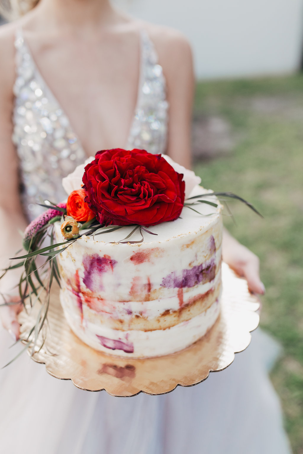 wedding cake topped with red flowers - photo by Alondra Vega Photography http://ruffledblog.com/jewel-toned-wedding-ideas-with-a-surprise-proposal