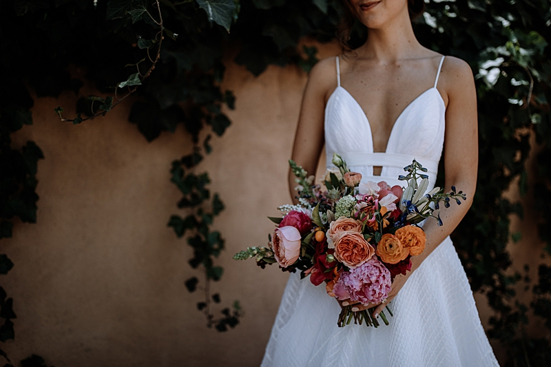 pink and orange wedding bouquets - https://ruffledblog.com/laid-back-los-poblanos-wedding-with-orange-bridesmaid-gowns