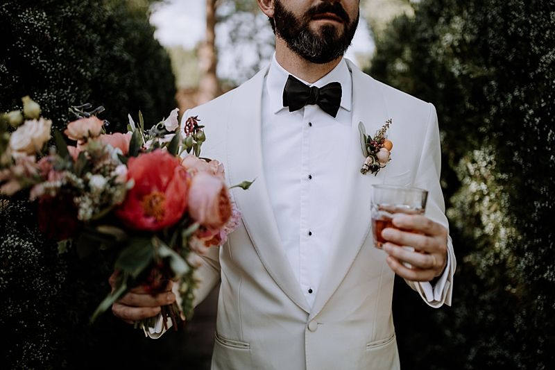 grooms in white tuxedos - https://ruffledblog.com/laid-back-los-poblanos-wedding-with-orange-bridesmaid-gowns