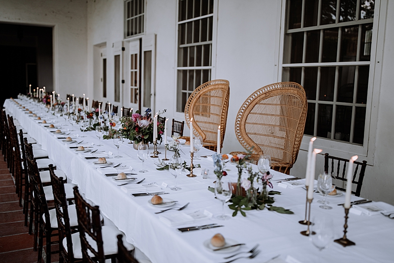 rattan chairs for the wedding sweetheart table - https://ruffledblog.com/laid-back-los-poblanos-wedding-with-orange-bridesmaid-gowns