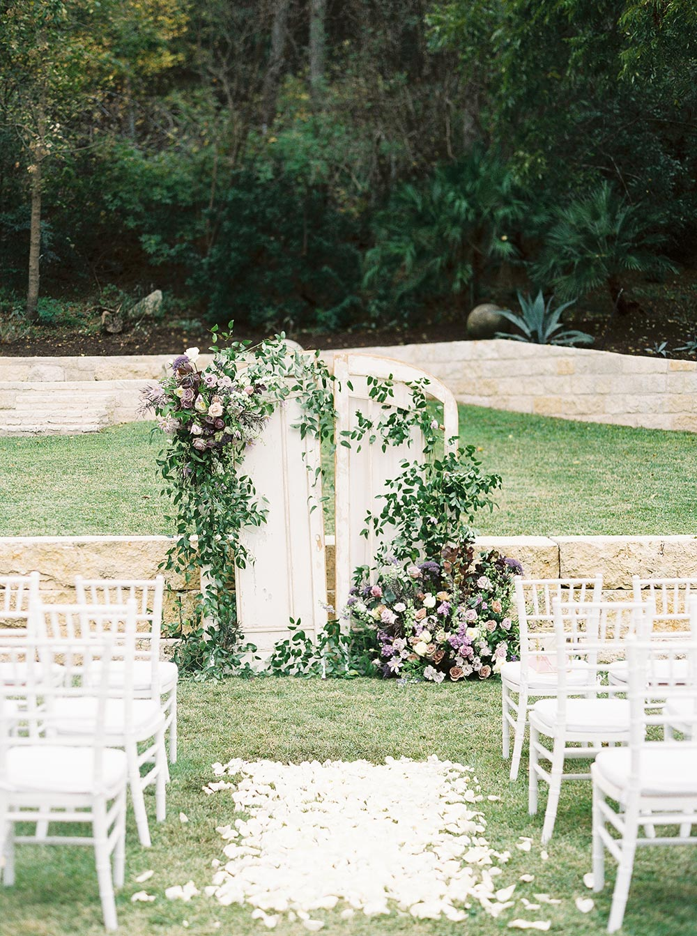 rustic chic wedding ceremony backdrop with purple and pink flowers