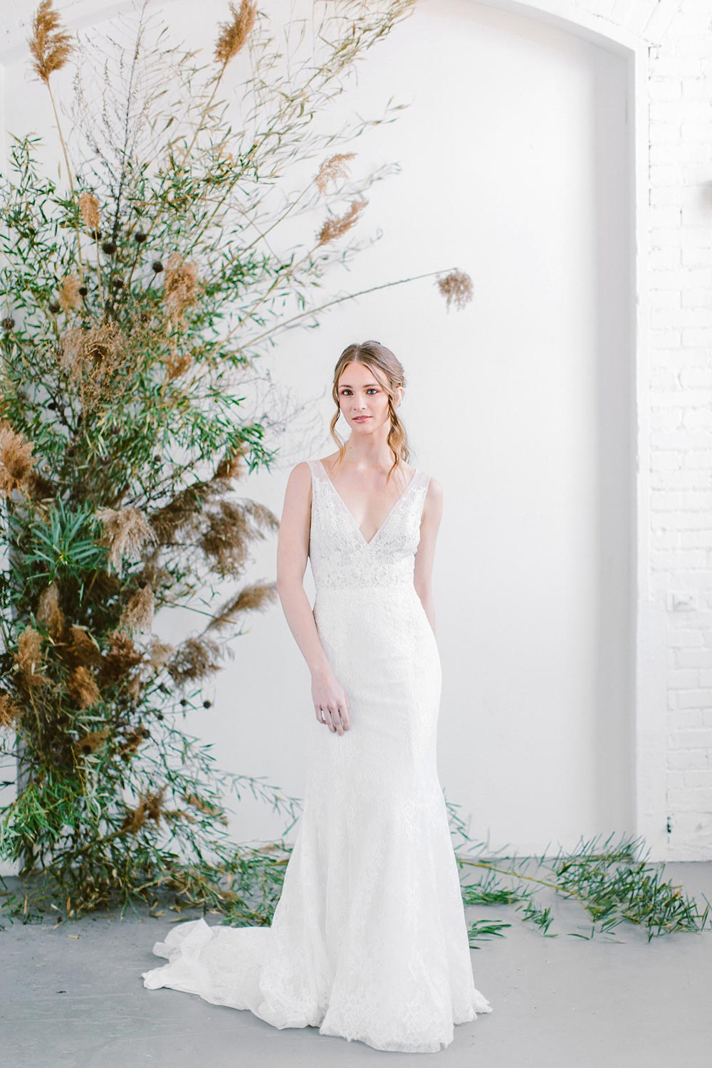 sheer v-neck lace wedding dress with fluted skirt and pampas grass backdrop