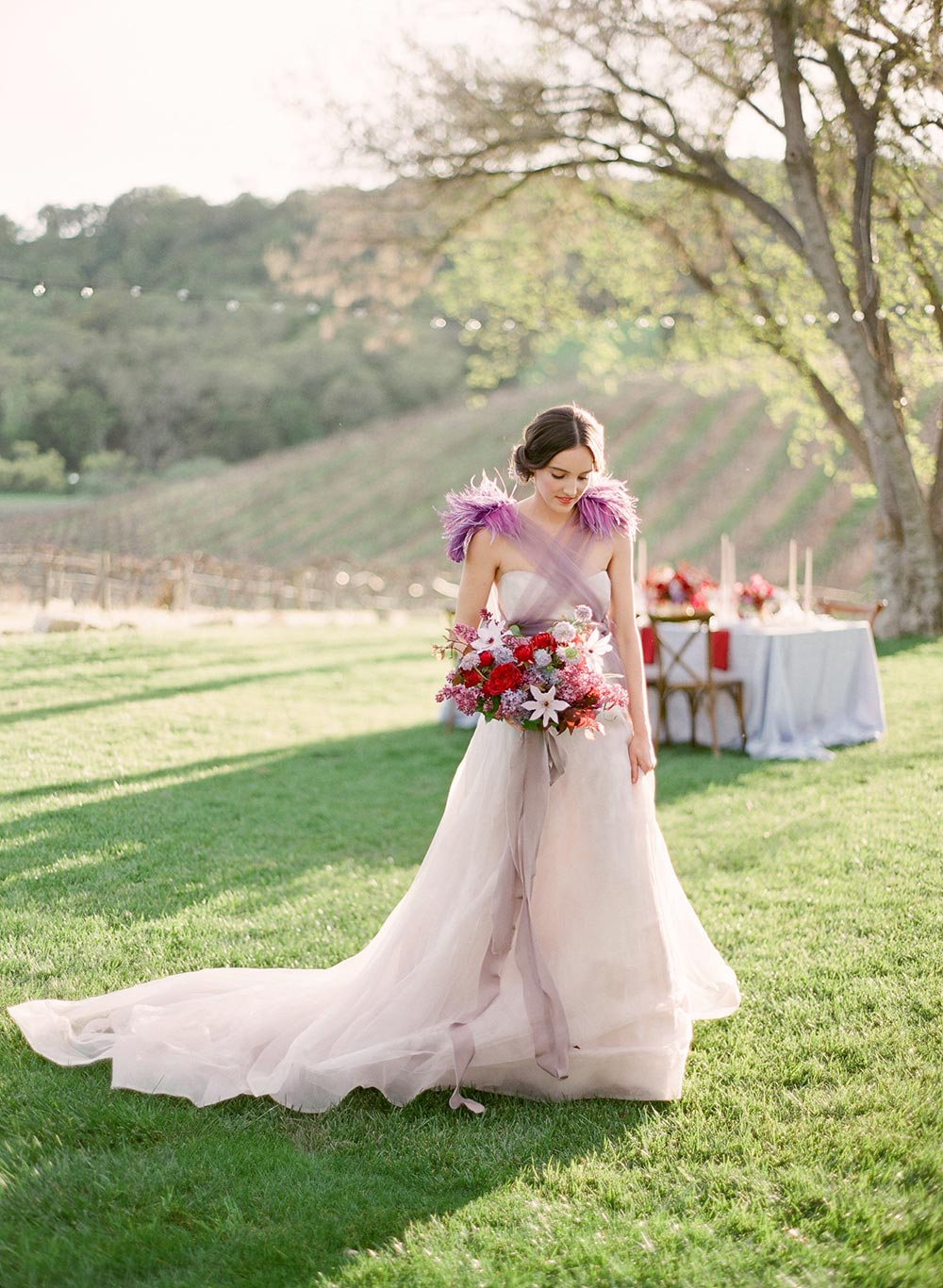 lavender wedding dress with feathers and tulle and a burgundy bridal bouquet