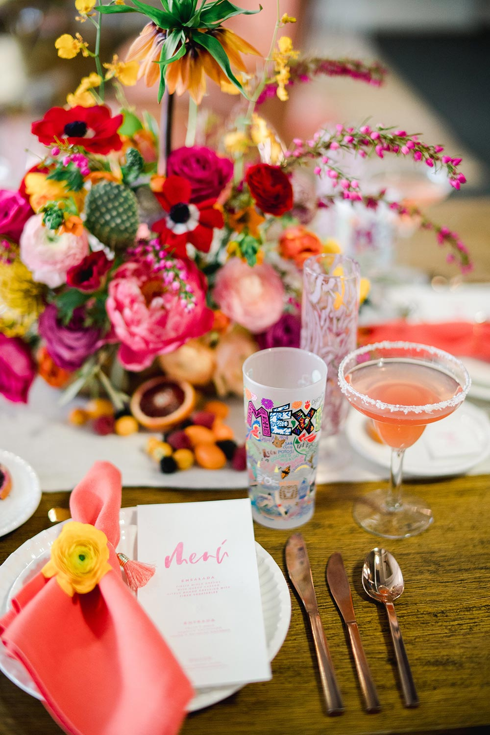 Cinco de Mayo wedding place setting with pink napkins, brush calligraphy menus and Mexico glass favors
