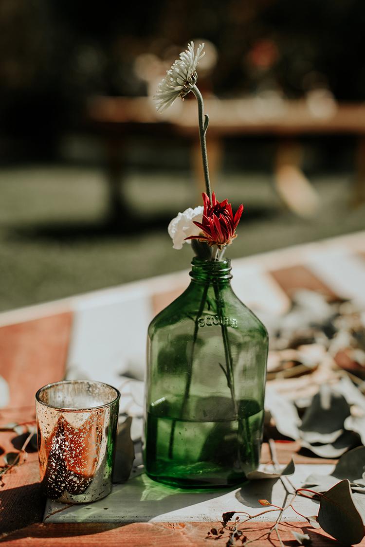 green glass wedding accents - https://ruffledblog.com/lovingly-handcrafted-backyard-wedding-with-boho-details