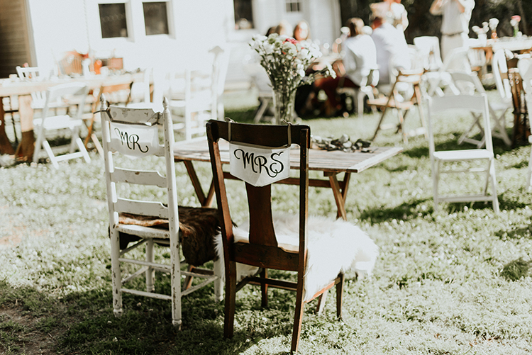 sweetheart table chair signs - https://ruffledblog.com/lovingly-handcrafted-backyard-wedding-with-boho-details