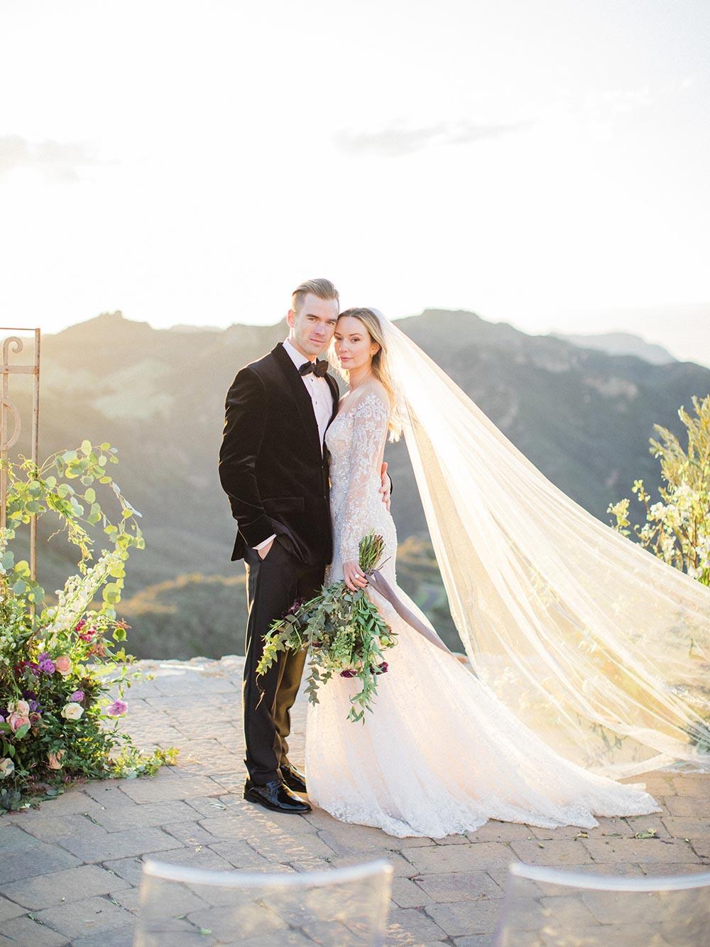 long sleeve embellished wedding dress with veil and black velvet groom tux