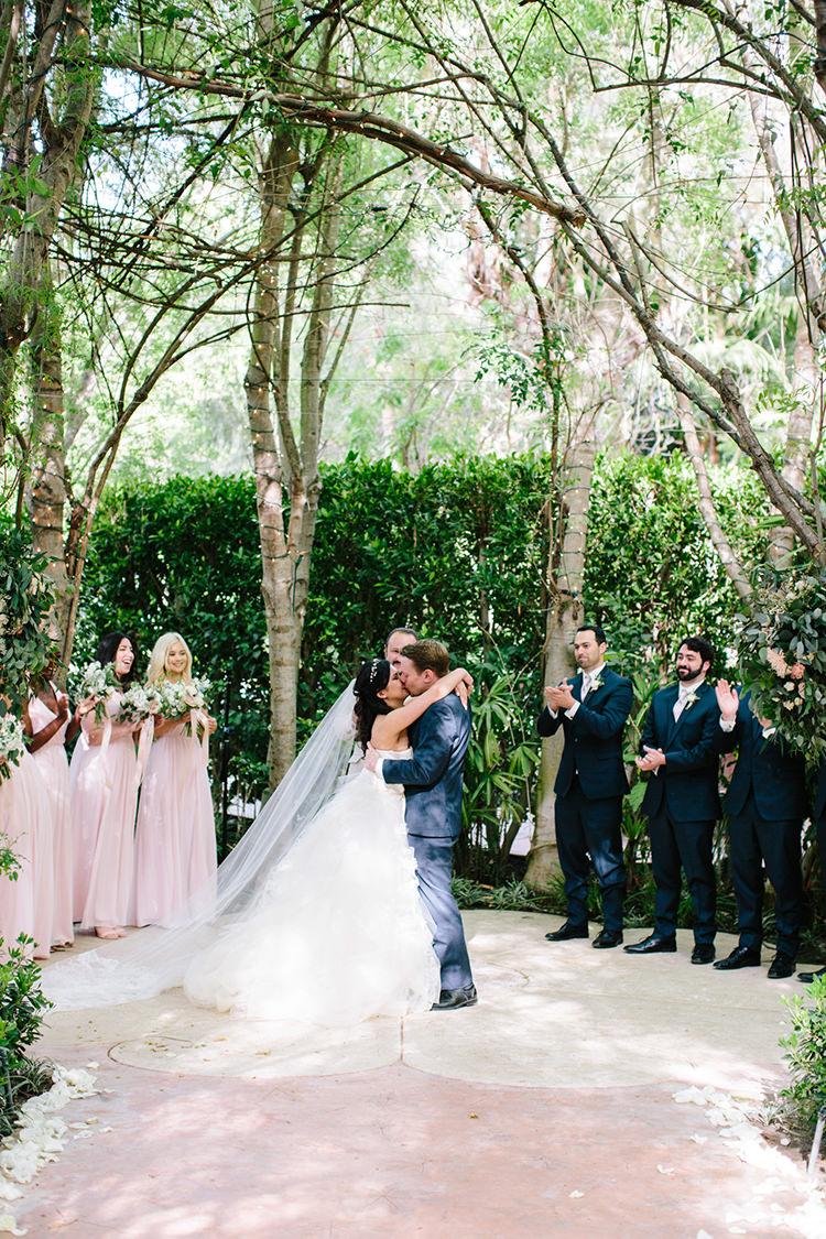 garden wedding ceremony kisses - photo by Mirelle Carmichael https://ruffledblog.com/magical-midsummer-nights-dream-wedding