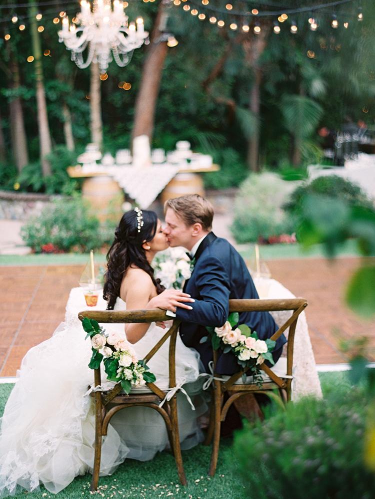 sweetheart table kiss - photo by Mirelle Carmichael https://ruffledblog.com/magical-midsummer-nights-dream-wedding
