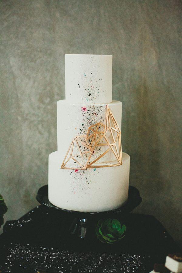 wedding cake with geometric accent and paint splatter - photo by Melissa Biador http://ruffledblog.com/40-eye-catching-geometric-wedding-ideas