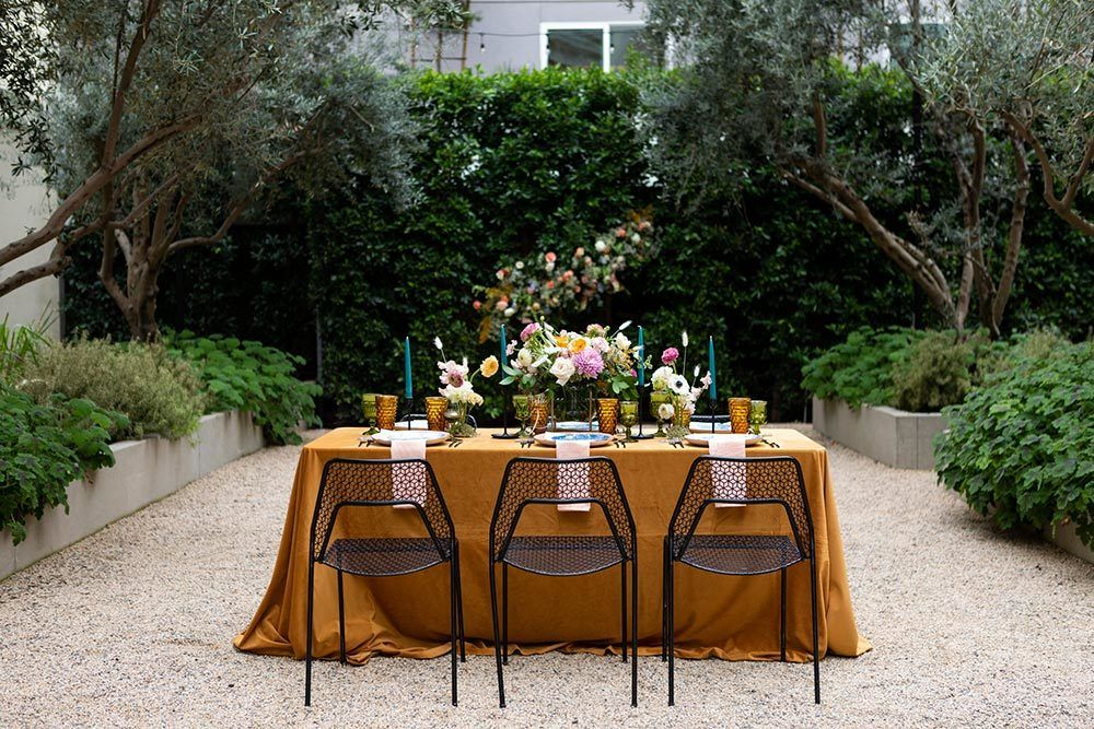 mustard tablescape with black wire chairs and marbled blue plates