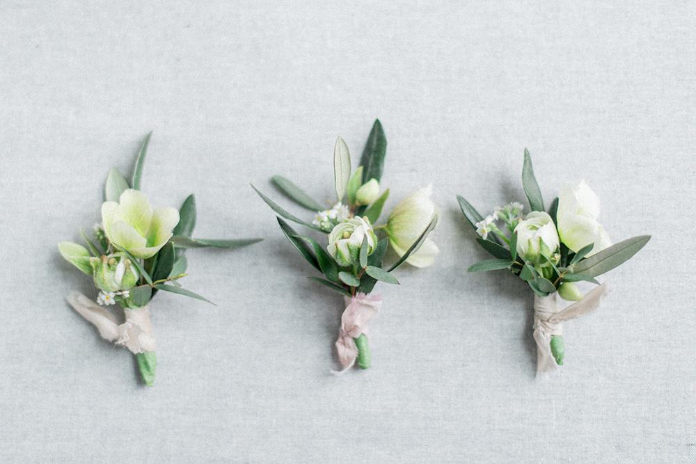greenery boutonnieres - photo by Laura Kelly Photography https://ruffledblog.com/minimalist-monochrome-european-wedding-inspiration