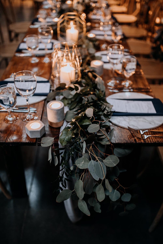 reception tables with eucalyptus runners - https://ruffledblog.com/modern-baltimore-mill-house-wedding