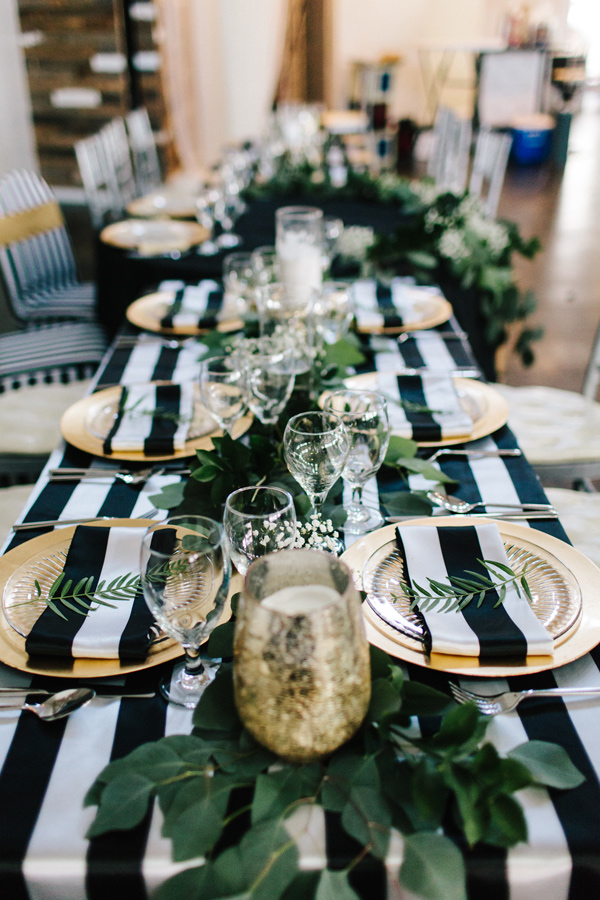 striped reception tablecloth - photo by Sarah Libby Photography https://ruffledblog.com/modern-black-and-white-wedding-with-emerald
