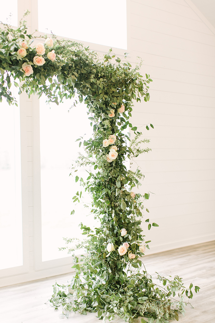 ceremony arch with flowers and greenery - photo by Mustard Seed Photography https://ruffledblog.com/modern-farmhouse-wedding-with-organic-details