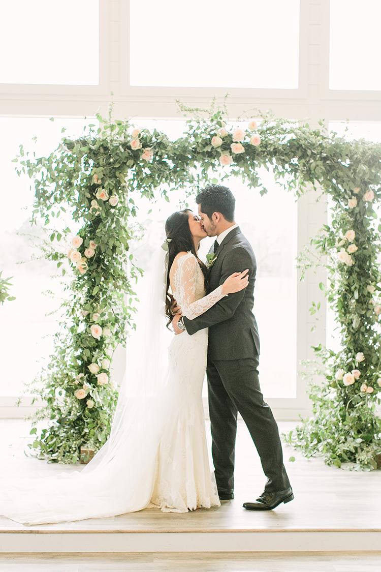 ceremony kiss - photo by Mustard Seed Photography http://ruffledblog.com/modern-farmhouse-wedding-with-organic-details
