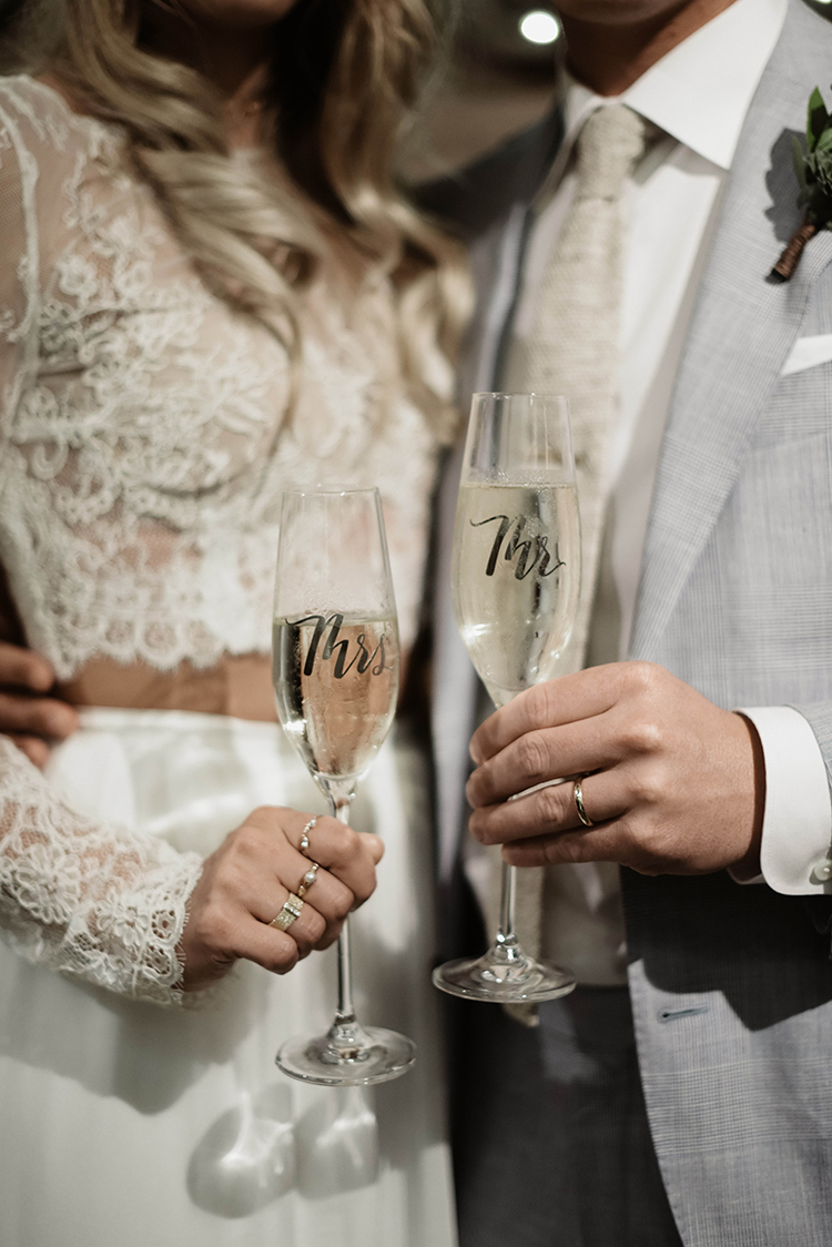 Mr and Mrs champagne flutes - photo by A Sea of Love https://ruffledblog.com/modern-industrial-wedding-with-lots-of-greenery