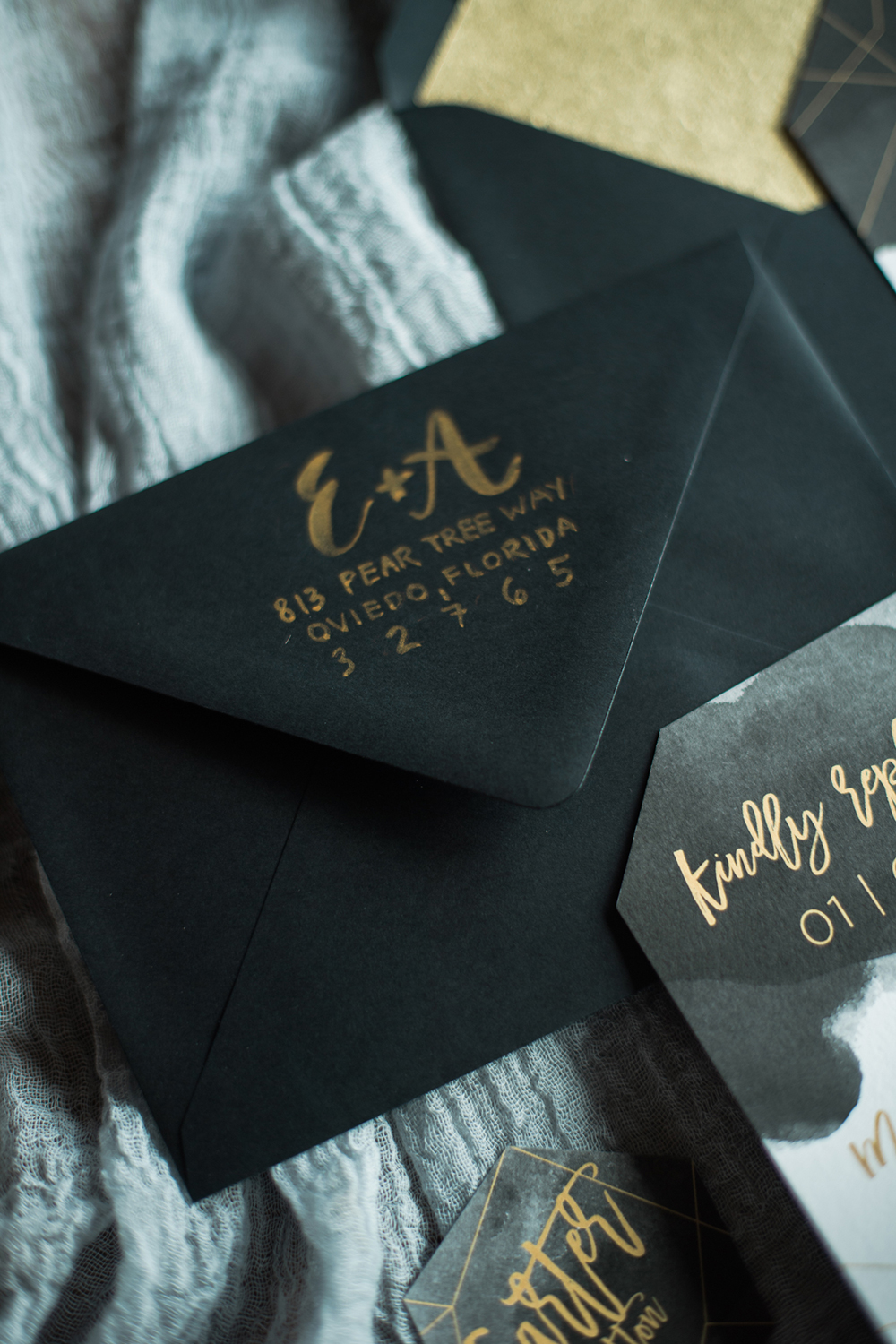black envelopes with gold calligraphy - photo by Kristen Weaver Photography http://ruffledblog.com/modern-organic-wedding-inspiration-with-greenery
