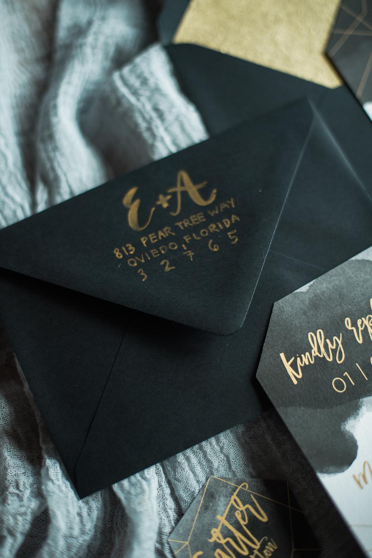black envelopes with gold calligraphy - photo by Kristen Weaver Photography https://ruffledblog.com/modern-organic-wedding-inspiration-with-greenery