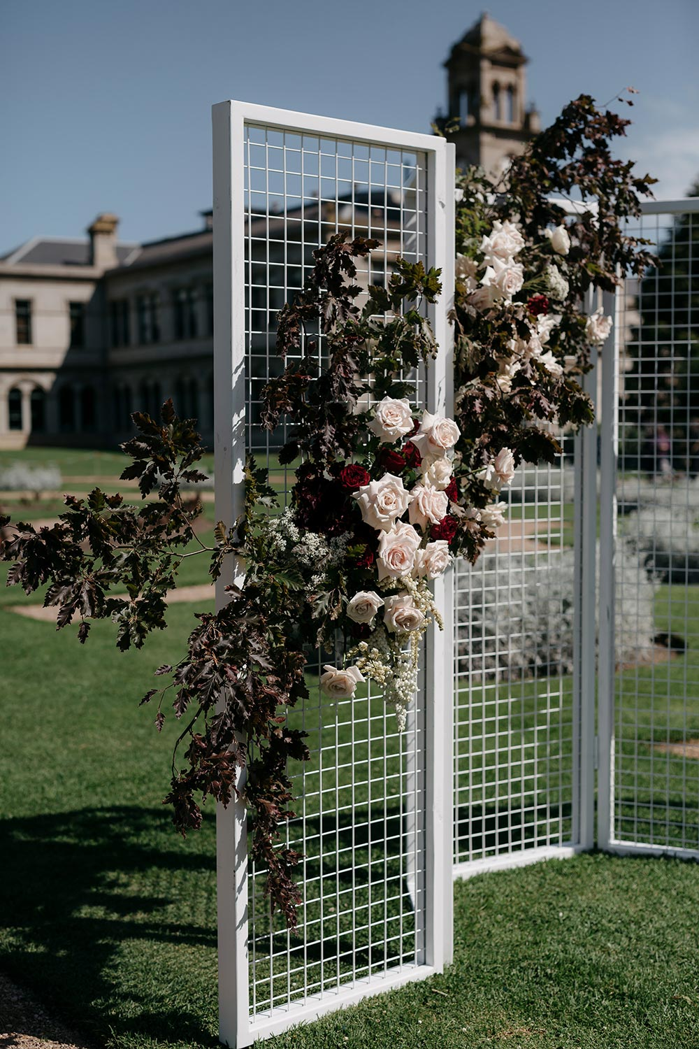 modern wedding ceremony backdrop with white grid panels and flowers