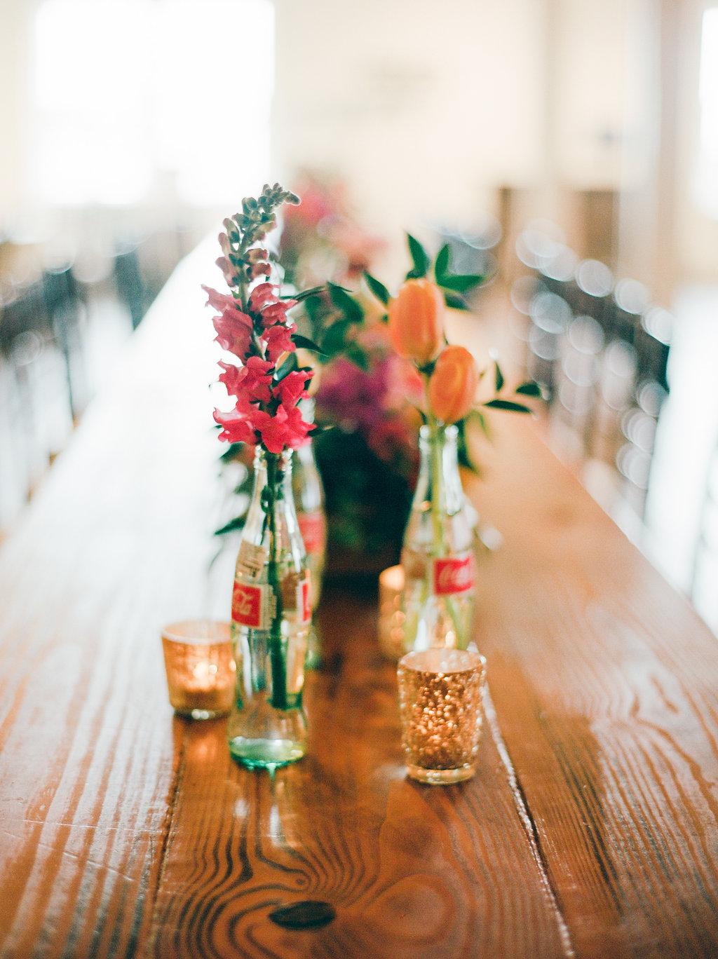 Coke bottle wedding centerpieces - https://ruffledblog.com/modern-playful-texas-carnival-wedding