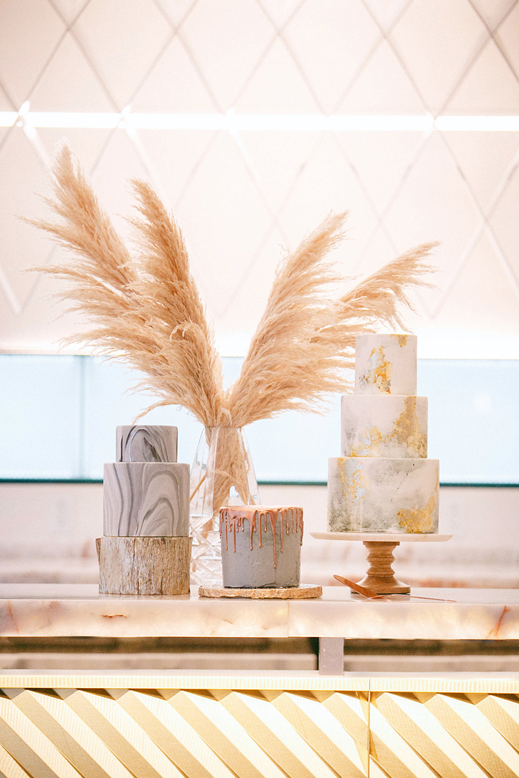 wedding cake tables - photo by Leigh Miller Photography https://ruffledblog.com/modern-wedding-inspiration-with-a-pampas-grass-chandelier