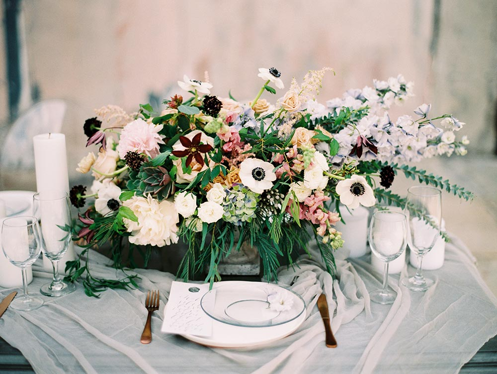 oversized centerpiece with moody color palette and clear plates