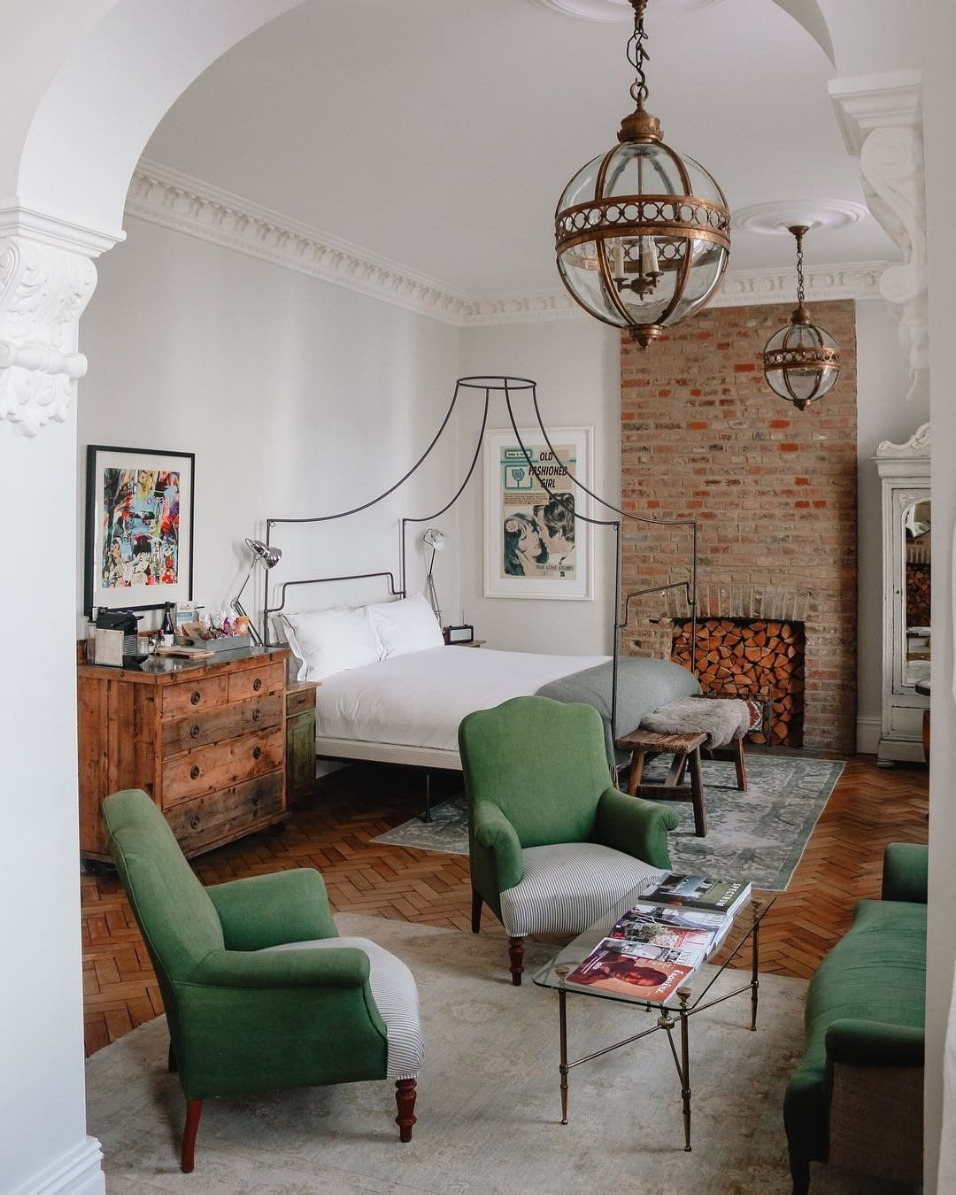 artistic London studio hotel room with green velvet chairs and canopy bed