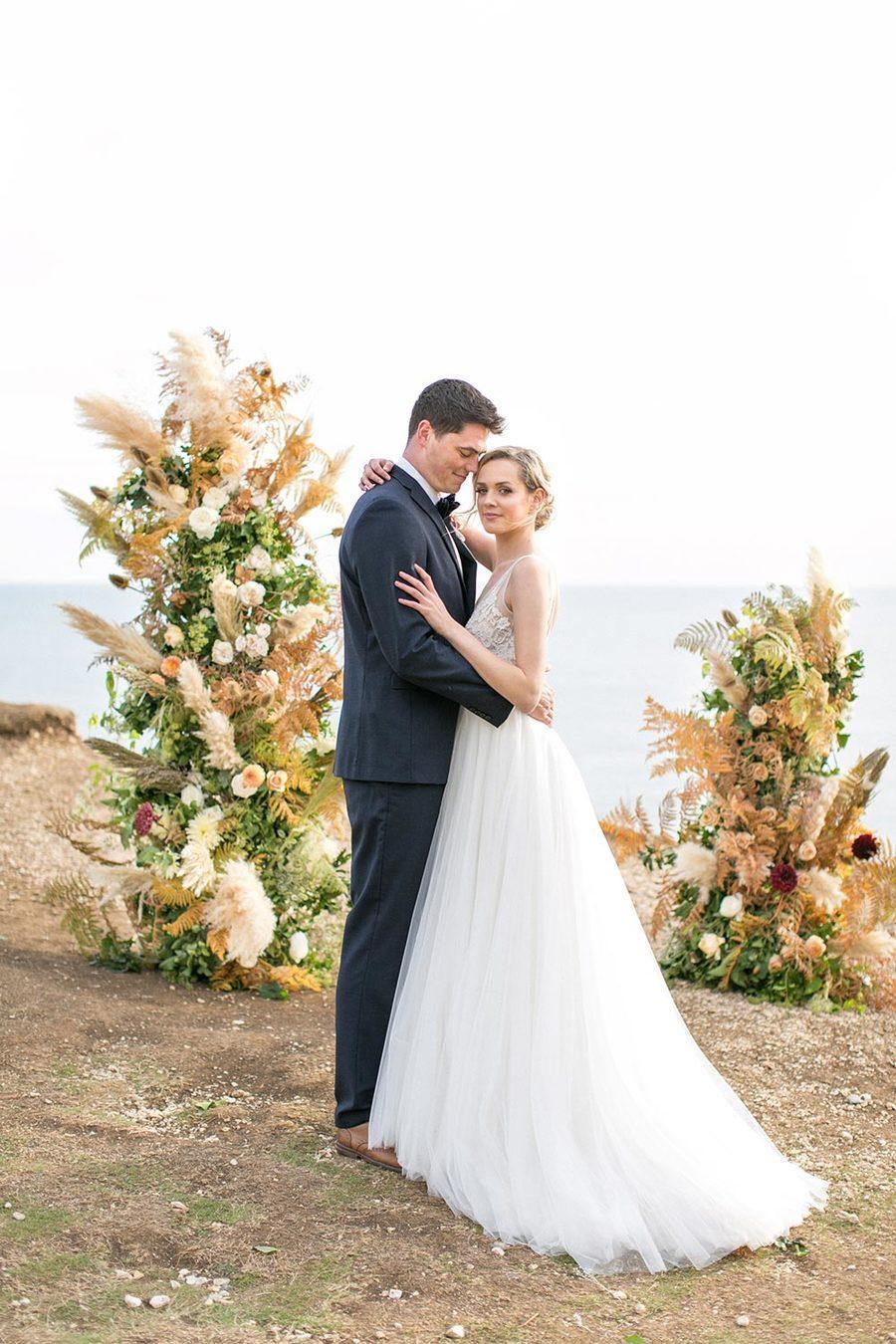 asymmetrical floral pillar wedding ceremony backdrop