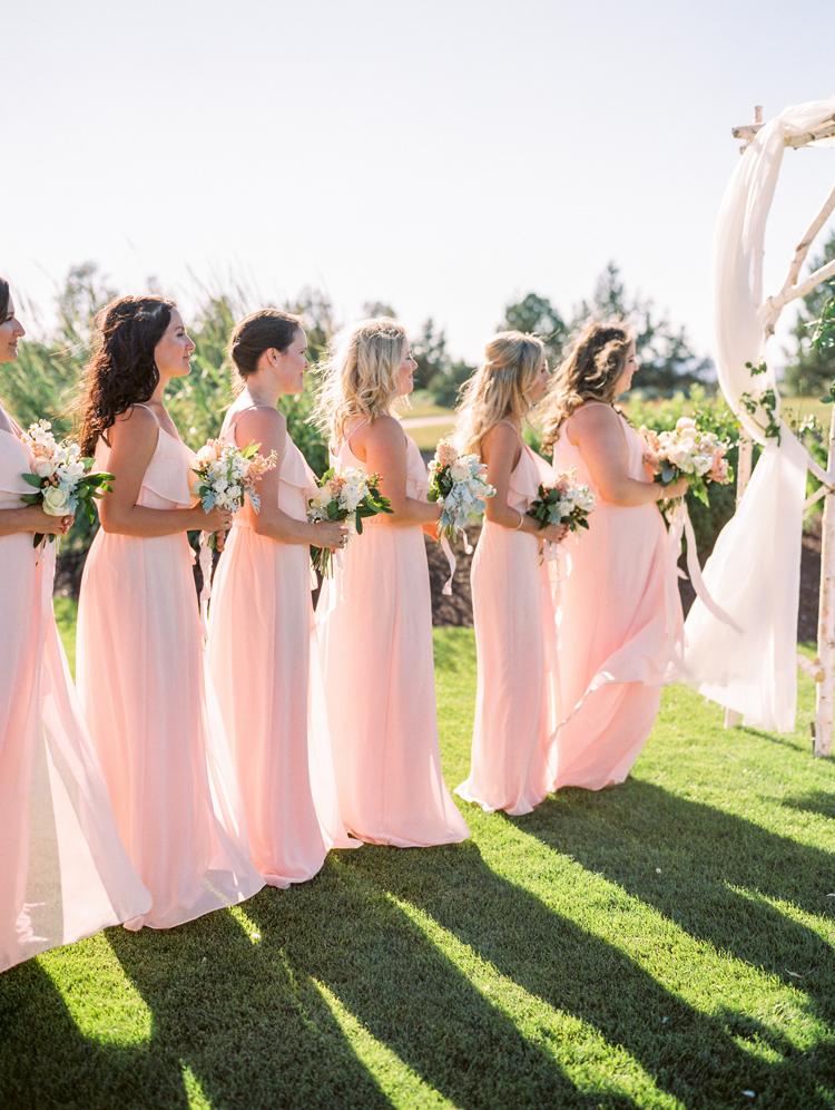 bridesmaids during ceremony - photo by Gabriela Ines Photography http://ruffledblog.com/oregon-resort-wedding-with-bohemian-style
