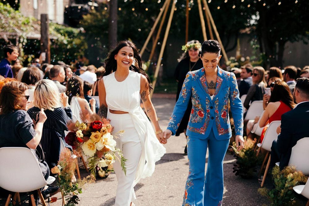 boho wedding ceremony with two brides in bridal suits