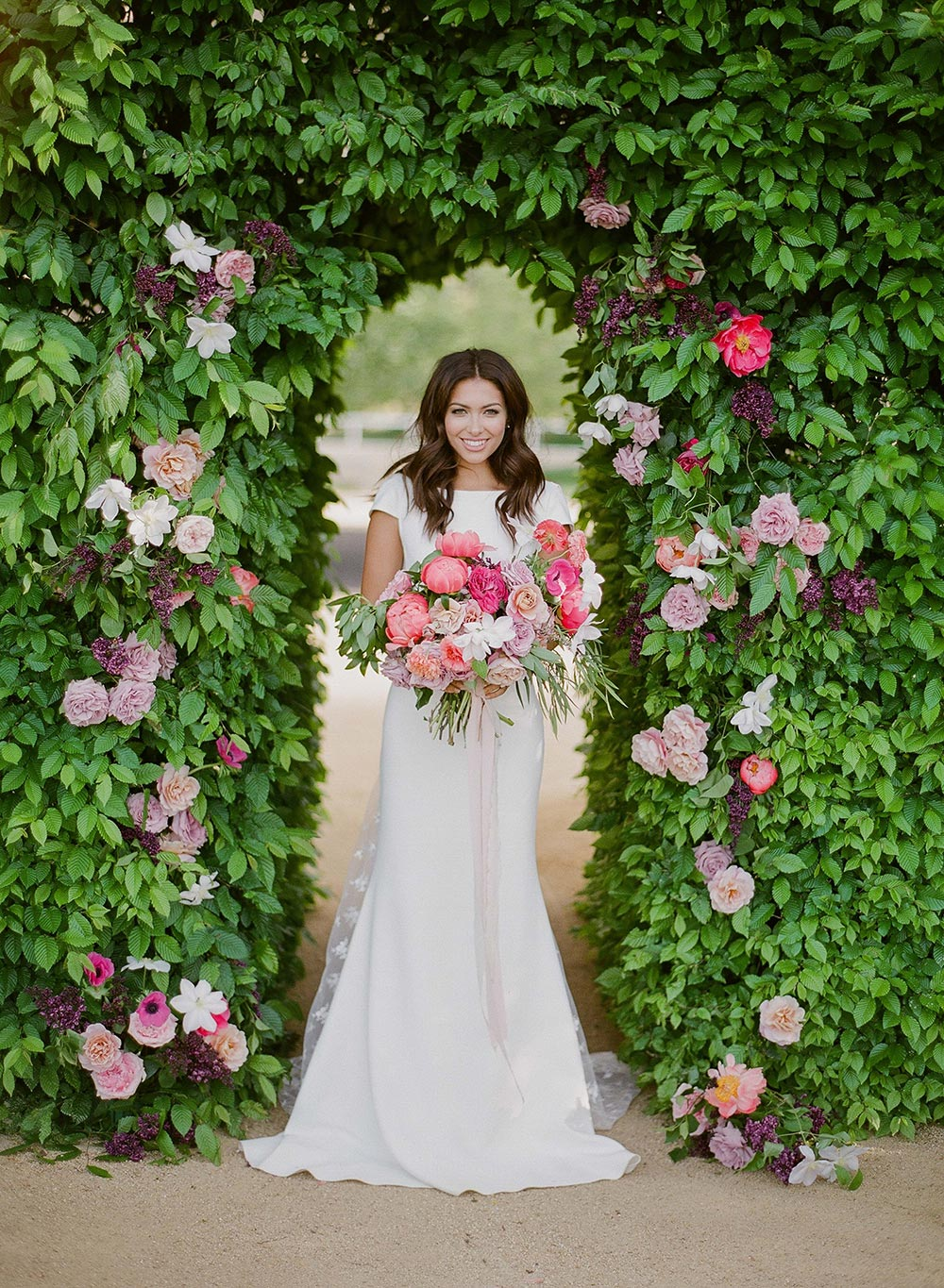 cap sleeve wedding dress with embellished train and poppy pink bouquet ceremony arch