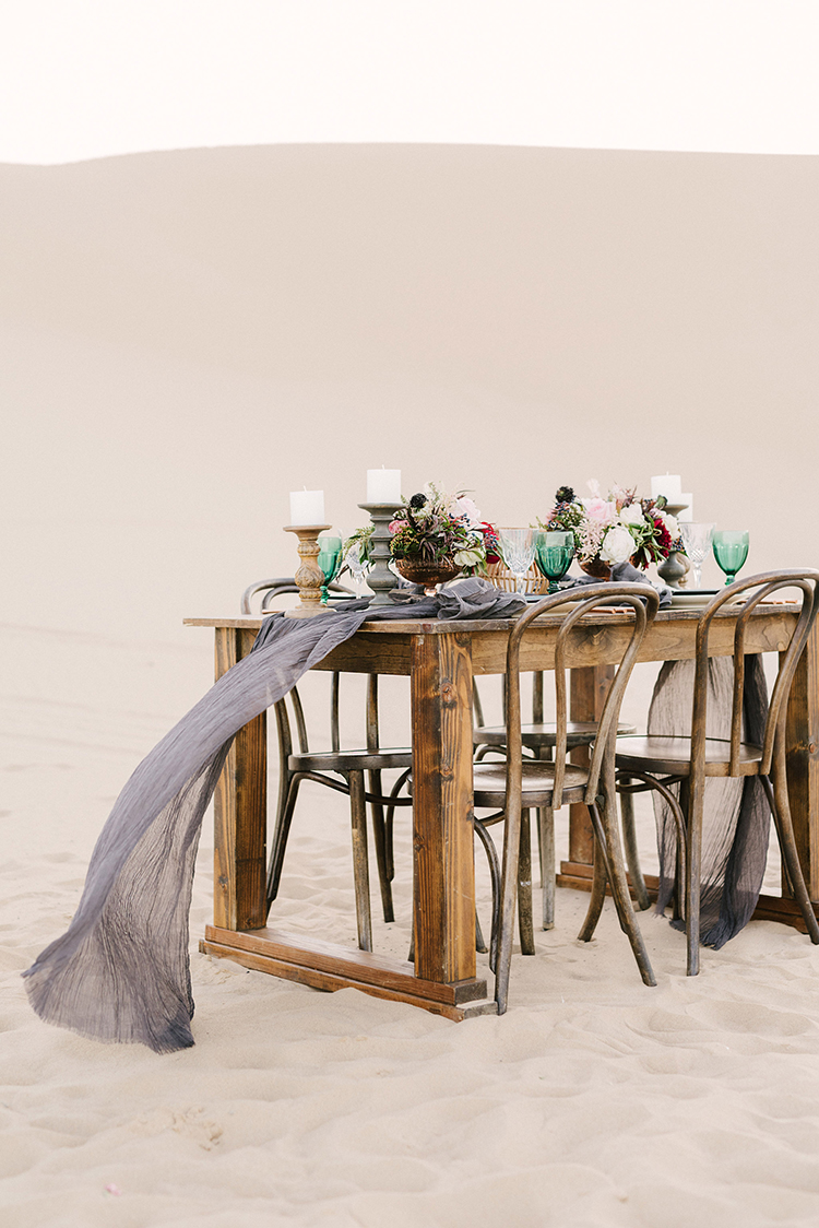 wedding tables in the desert - photo by Saje Photography http://ruffledblog.com/real-sand-dunes-elopement-with-a-black-wedding-gown