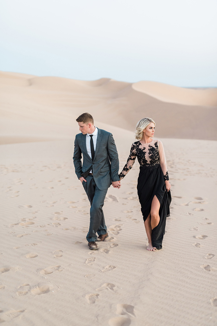 sand dune weddings - photo by Saje Photography https://ruffledblog.com/real-sand-dunes-elopement-with-a-black-wedding-gown