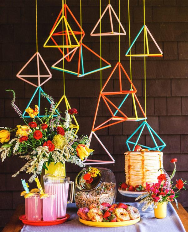 neon hanging geometric cake table backdrop - photo by Rodeo and Co https://ruffledblog.com/40-eye-catching-geometric-wedding-ideas