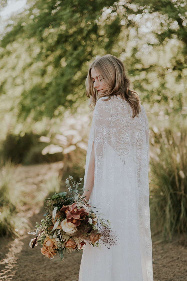 lace cape wedding dresses - photo by Shelly Anderson Photography http://ruffledblog.com/san-diego-safari-park-glamping-wedding-editorial