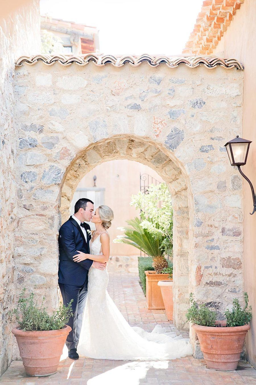 Mediterranean wedding venue with designer bridal gown and custom navy groom suit