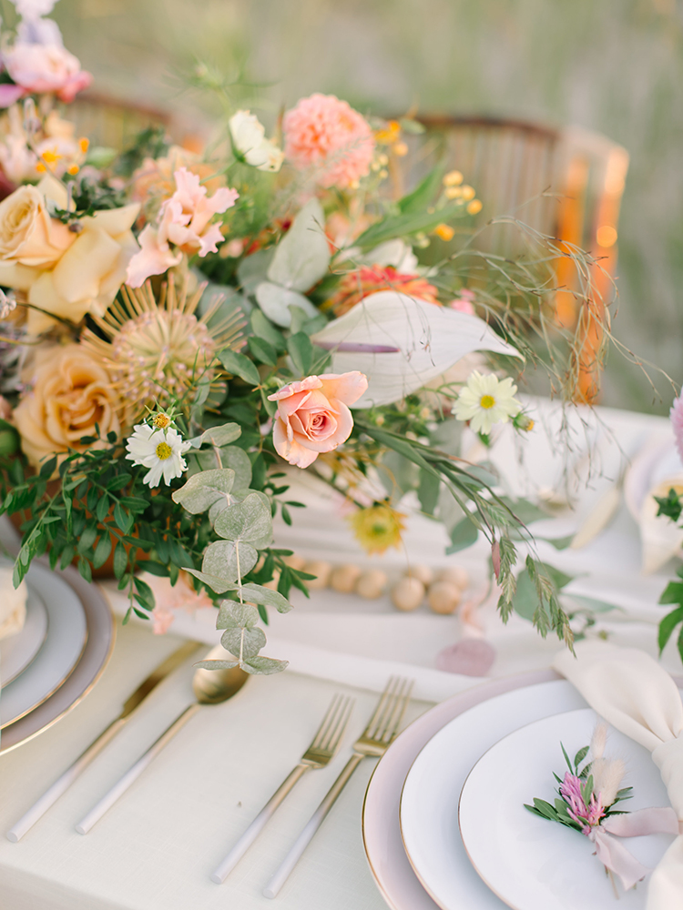 yellow and pink floral arrangements - https://ruffledblog.com/september-sunsets-wedding-inspiration-with-a-vw-bus