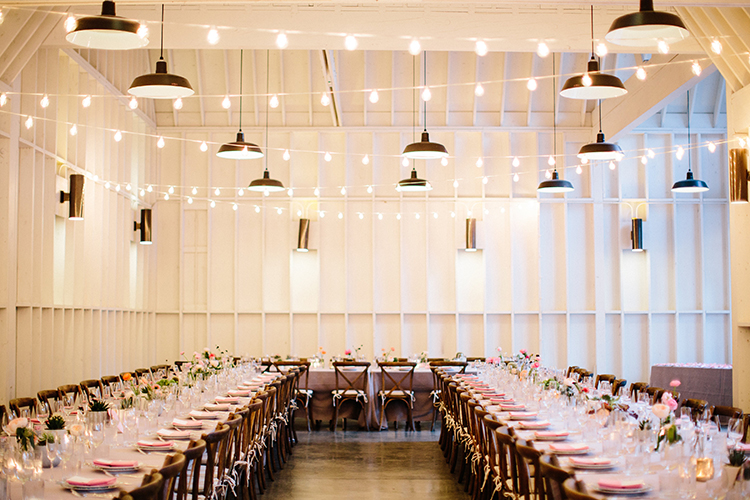 industrial wedding reception with market lights - photo by Birds of a Feather http://ruffledblog.com/soft-and-romantic-wedding-at-lombardi-house