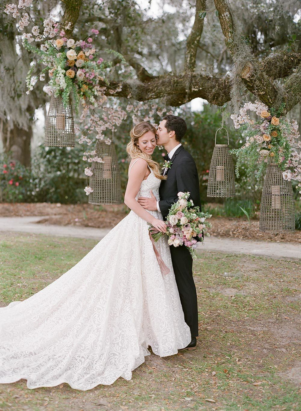 embroidered wedding dress with sweetheart neckline and black groom tux with live oak wedding backdrop and floral lanterns