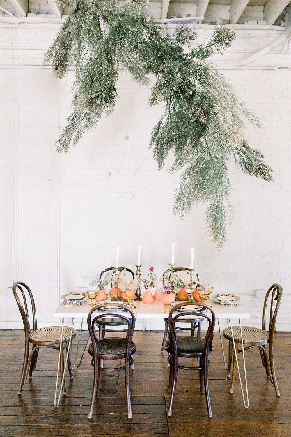 modern earth toned wedding inspiration with greenery floral installation
