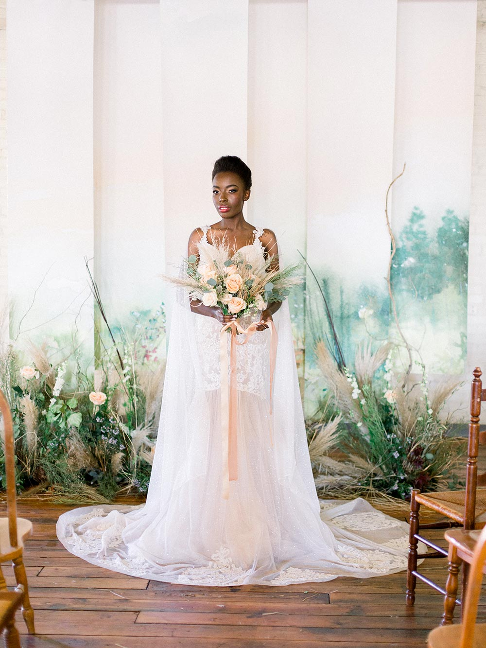 shimmery bridal gown with wing panels and a watercolor mural backdrop with wild overgrown flowers