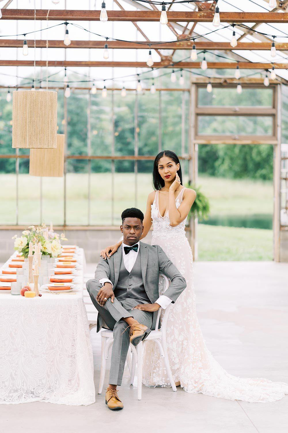 floral applique wedding dress with gray groom suit and glass house wedding reception with boho pendants