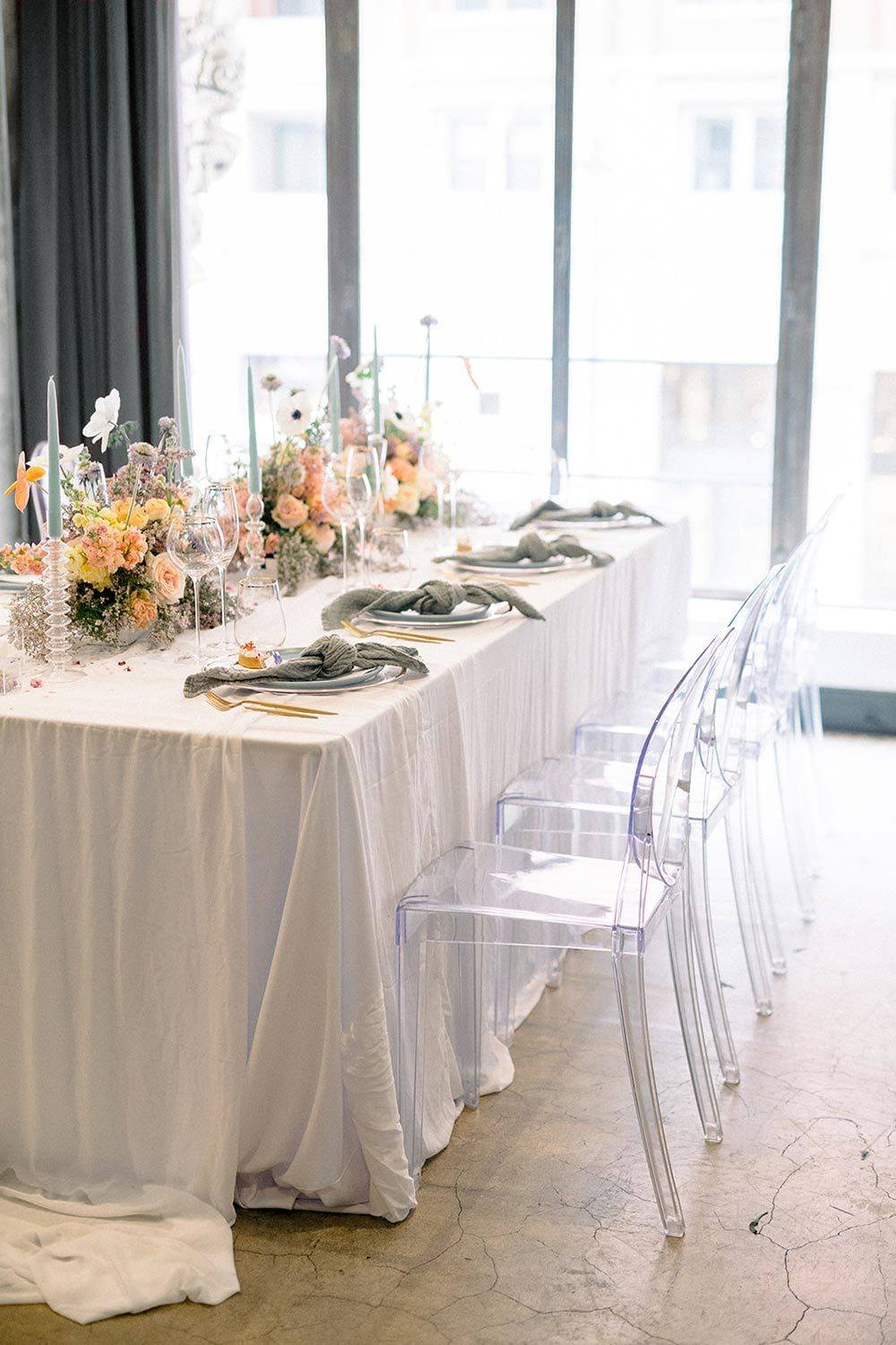 indoor wedding tablescape with ghost chairs and blue and peach centerpieces