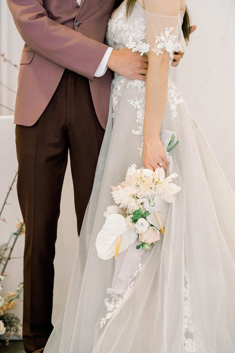 off-the-shoulder wedding dress with dusty blue tulle and lace and dusty pink groom suit