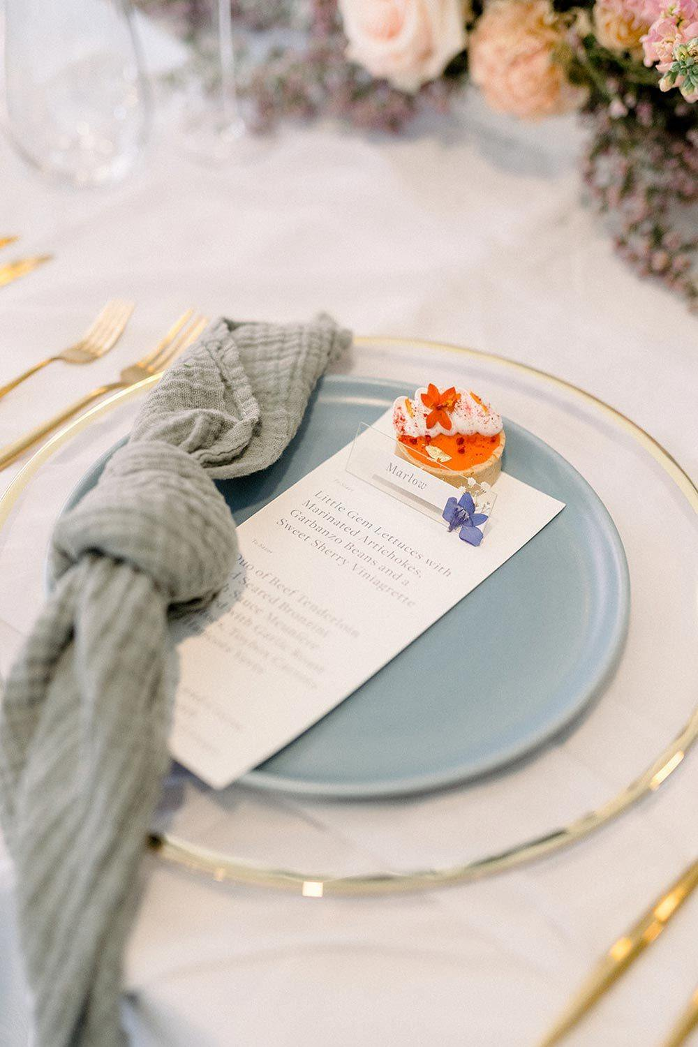 pale blue wedding place setting with cloth napkin and edible favor